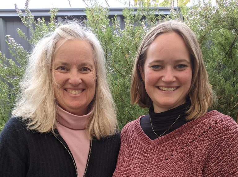 Dana and Hannah, side by side facing the camera and smiling.